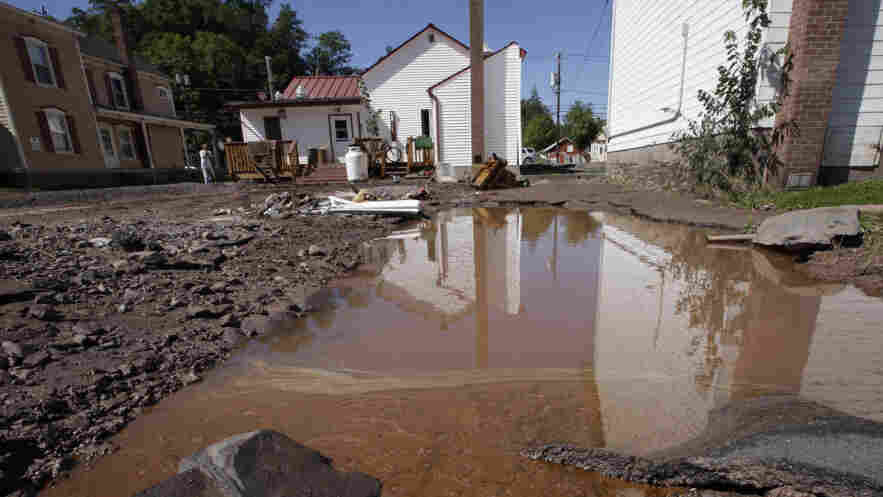 Water mixed with gasoline accumulated in the Zerega's pizzeria parking lot last month in Windham, N.Y. More than a dozen towns in Vermont and at least three in New York were cut off, with roads and bridges washed out by flooding caused by Tropical Storm Irene.