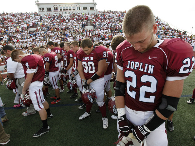 Football players observe a moment of silence before Joplin High School's home opener Saturday. The Missouri city has tried to recover from billions of dollars in damage from a tornado in May.