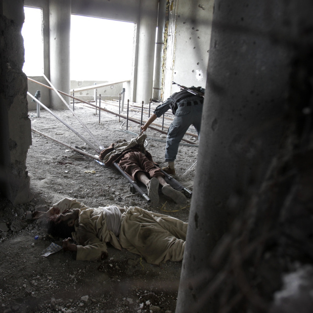 Inside the building from which the attack was staged, an Afghan soldier checked one attacker's body earlier today. Another dead insurgent lies nearby. Bullet holes riddle the walls.