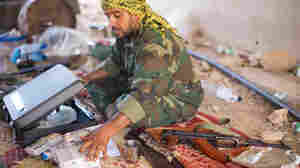 A fighter loyal to the Transitional National Council sits with money that has been donated to pay fighters at a checkpoint outside Bani Walid, Libya, on Monday. It was widely feared that ousted leader Moammar Gadhafi and his supporters spirited away much of the country's wealth. But those fears have yet to materialize, as Libya's central bank holdings appear to remain largely intact.