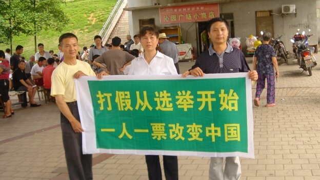 """Labor activist Liu Ping (center) has unleashed a wave of candidates in the latest round of local elections. Here, she and two other campaigners hold a banner that declares, """"Fighting fake  [things] should start with elections. One person, one vote will change  China."""""""