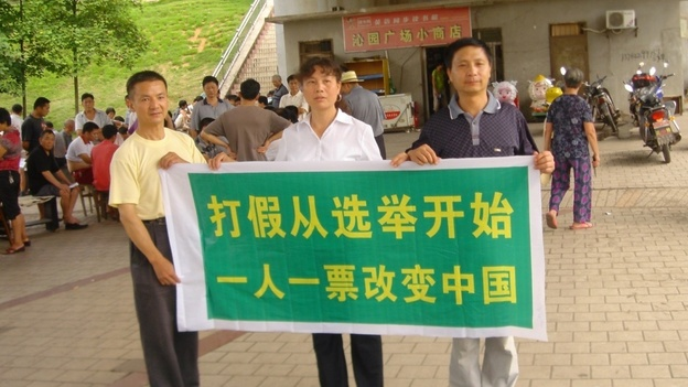 "Labor activist Liu Ping (center) has unleashed a wave of candidates in the latest round of local elections. Here, she and two other campaigners hold a banner that declares, ""Fighting fake  [things] should start with elections. One person, one vote will change  China."" (Courtesy of Liu Ping)"