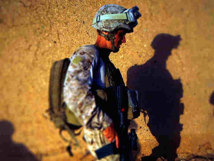 Darryl St. George, a Navy corpsman, walks along  a mud compound wall in Helmand province, southern Afghanistan. Next month will mark 10 years for U.S. forces in Afghanistan.