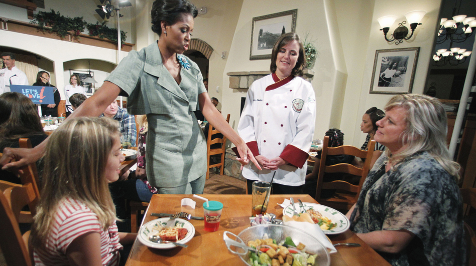 First Lady Michelle Obama, accompanied by Darden chef Julie Elkinton, talks to Charisse McElroy, right, and her daughter Jacqueline McElroy, 9, during an event at Olive Garden in Hyattsville, Md. on Thursday.
