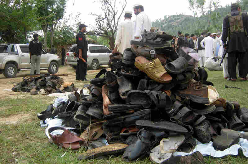 Pakistani villagers and officials collect shoes at a funeral ceremony after a suicide bomb struck in Lower Dir, Pakistan, on Thursday.