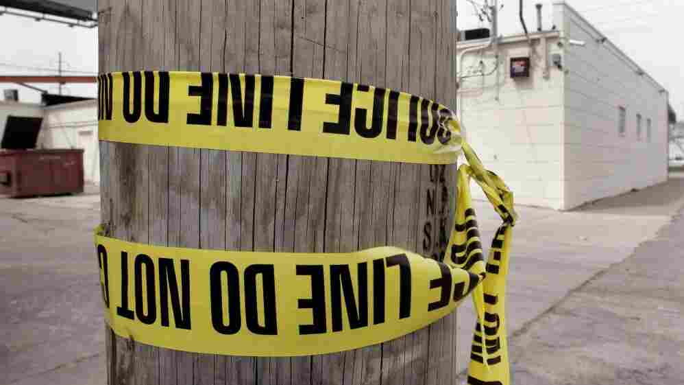 Crime scene tape is wrapped around a telephone pole in Detroit.