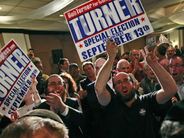 A crowd cheers as Republican Bob Turner appears on stage during an election night party on Tuesday in New York. The traditionally Democratic and Jewish district elected Turner, revealing the problems Obama may have with political strongholds in the 2012 election.