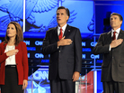 Republican presidential candidates (from left) Rep. Michele Bachmann, former Massachusetts Gov. Mitt Romney and Texas Gov. Rick Perry cover their hearts during the playing of the national anthem before a Republican presidential debate on Sept. 12.