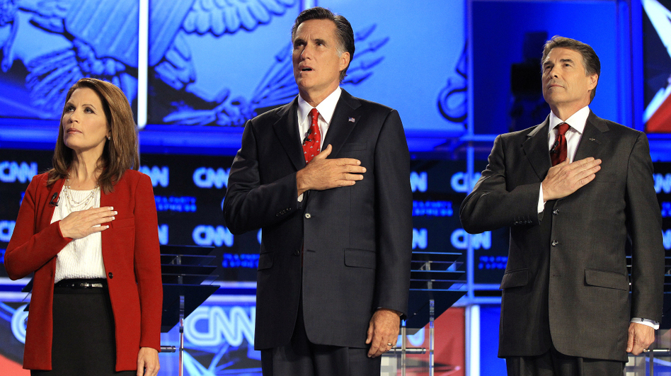 Republican presidential candidates (from left) Rep. Michele Bachmann, former Massachusetts Gov. Mitt Romney and Texas Gov. Rick Perry cover their hearts during the playing of the national anthem before a Republican presidential debate on Sept. 12. (Chris O'Meara/AP)