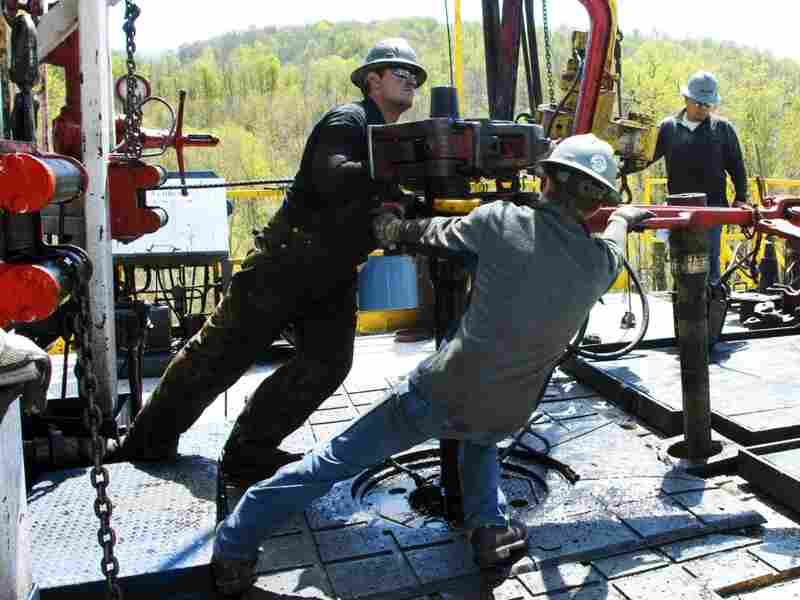Workers move a section of well casting at a natural gas well site in Pennsylvania. Energy expert Daniel Yergin says that in addition to trucks and traffic, natural gas production can bring jobs and economic growth to gas-rich areas.