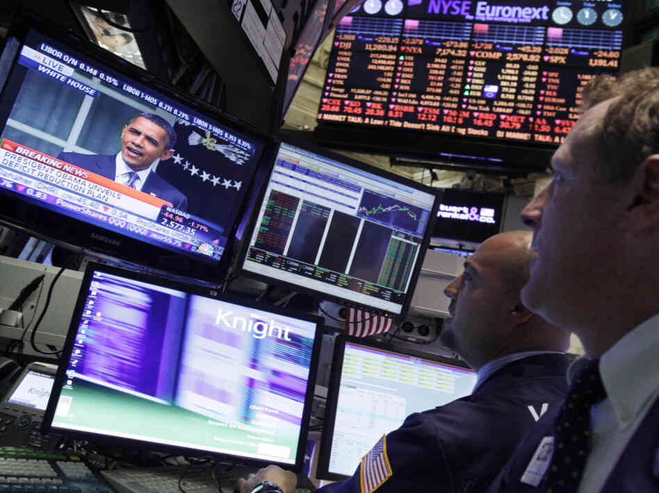 Specialists on the floor of the New York Stock Exchange watch President Obama's televised speech on debt reduction Monday. Obama wants to require investment fund managers to pay at l