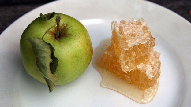 A small green apple next to a stack of honeycomb chunks on a plate