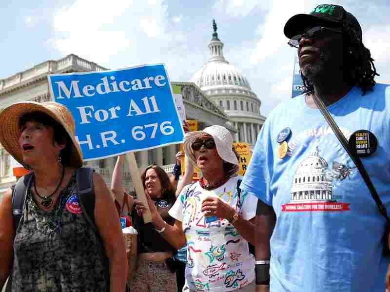 Activists hold signs as they march on Capitol Hill after a rally on  healthcare July 30, 2009 in Washington, DC. Activists gathered on the Hill for a single payer model healthcare reform and  celebrate the 44th birthday of Medicare.