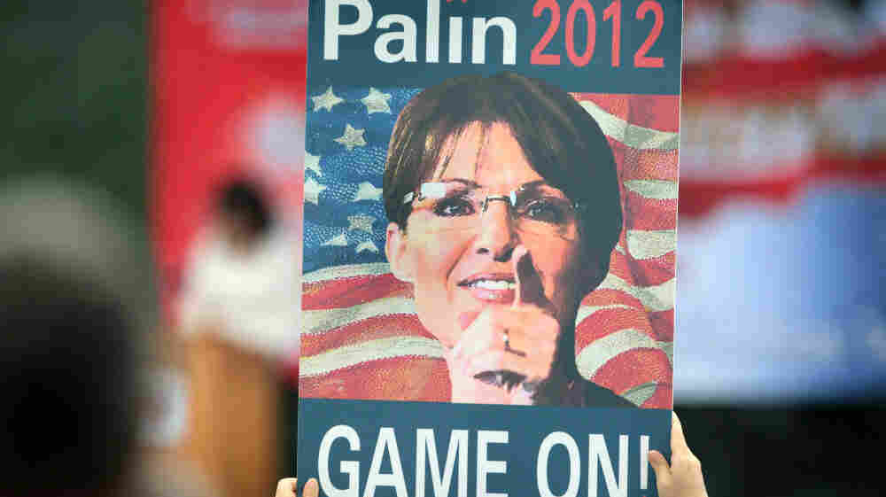 """A supporter holds up a sign as former Alaska Gov. Sarah Palin speaks during the Tea Party of America's """"Restoring America"""" event at the Indianola Balloon Festival Grounds in Indianola, Iowa."""