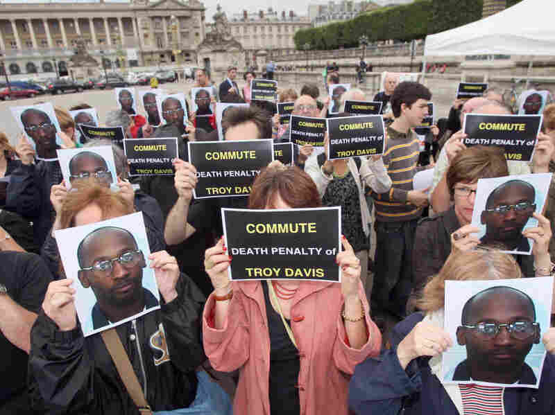 During a 2008 protest in support of death row inmate Troy Davis, people in Paris' Place de la Concorde hold signs urging clemency for Davis, convicted of killing a police officer in 1989.