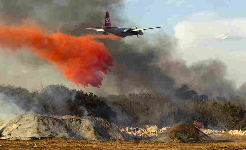 A plane dumps fire retardant on a 30-acre grass fire in Leander. The blaze destroyed 15 homes.