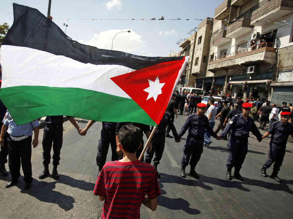 A boy holds Jordan's national flag at a protest calling for King Abdullah II to institute more constitutional reforms in Amman, Sept. 9. Security forces formed a human chain to keep demonstrators at bay.