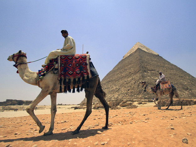 Tourist guides sit on camels as they wait for clients next to the Giza pyramids on the outskirts of Cairo, Egypt, June  23. Tourism in Egypt has dropped 35 percent overall in the first half of this year compared with the same period in 2010.