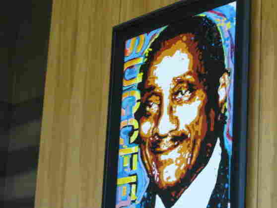 """A portrait of Johnson Publishing Co. founder John H. Johnson hangs in the company's lobby, embellished with the word """"succeed."""" Ebony's September issue included an article on how to raise a high achiever."""