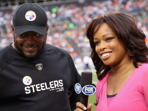 Pam Oliver,  sideline reporter for Fox Sports, interviews head coach Mike Tomlin of  the Pittsburgh Steelers as he leads his team against the Denver Broncos.