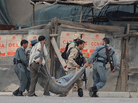 Afghan security personnel carry a wounded colleague across a street in Kabul on Sept. 14, after Taliban fighters attacked the most heavily protected part of the Afghan capital. Adm. Mike Mullen, chairman of the Joint Chiefs of Staff, said Thursday before a Senate panel that the Haqqani network of militants, supported by Pakistan, was responsible for this attack, among others.