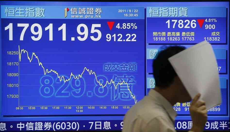 A man walk past a screen showing Hong Kong's benchmark Hang Seng stock index diving Thursday. Indexes around the world fell sharply amid worries about the global economy.