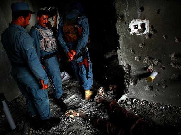 Sept. 13: Afghan Security personnel stand above the body of one attacker, on the 10th floor o