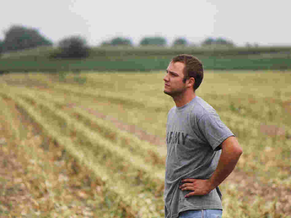 Austin Bruns stands on land owned by a contractor for Monsanto, an agriculture corporation. Bruns helps with seed corn production there, and also rents 150 acres elsewhere.