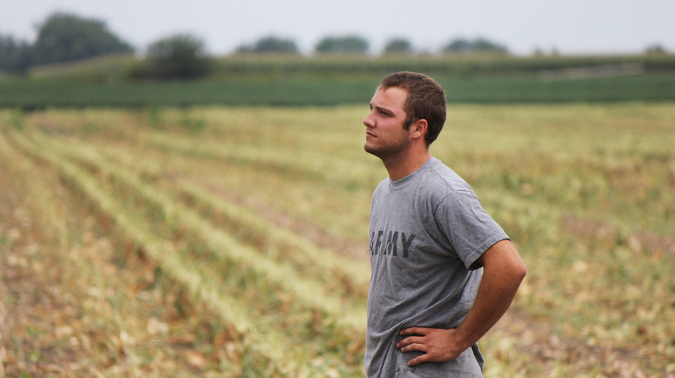 Austin Bruns stands on land owned by a contractor for Monsanto, an agriculture corporation. Bruns helps with seed corn production there, and also rents 150 acres elsewhere. (Clay Masters for NPR)