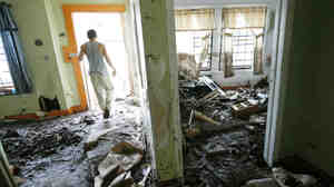 Justin Mudge walks through the muddy interior of his great uncle's gun shop, destroyed by flooding caused by Irene on Sept. 1 in Prattsville, N.Y. FEMA will run out of money to help disaster victims by early next week unless Congress acts.