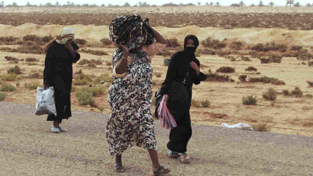 Libyans flee on foot along the main road heading west, away from Sirte, on Tuesday. Sirte, cut off from the rest of the country, is the last major town controlled by forces loyal to toppled dictator Moammar Gadhafi.