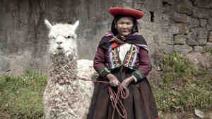 A woman stands with her alpaca in Peru.