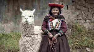 A woman stands with her alpaca in Peru.