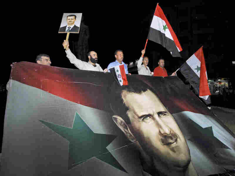 Supporters of Syrian President Bashar Assad carry a giant flag with his image on it during a pro-regime protest in Damascus, Syria, in August. Pro-government forces are now taking their message to a new arena: cyberspace.
