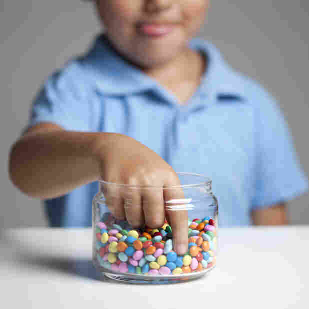 Boy taking candy from a jar
