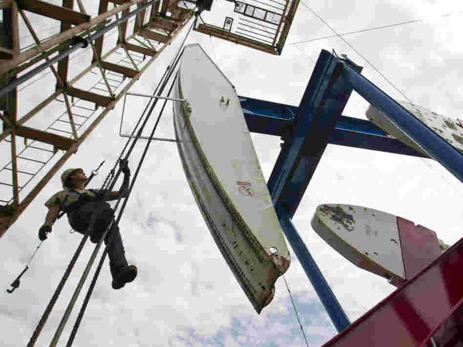 Ben Shaw hangs from an oil derrick outside Williston, ND, in July 2011. Williston's mayor, Ward Koeser, estimates that the town has between 2,000 and 3,000 job openings for oil workers.