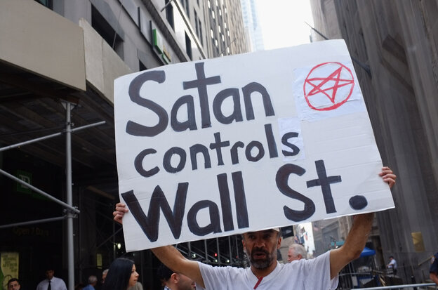 A demonstrator holds up a sign in front of the  New York Stock Exch
