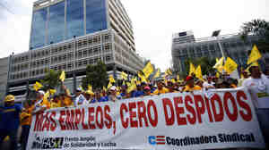 "Public workers march with a banner that reads in Spanish ""More jobs, zero layoffs"" in San Juan on Oct. 15, 2009. Thousands of protesters gathered at Puerto Rico's financial hub to demonstrate against Gov. Luis Fortuno and the layoffs of more than 20,000 public employees."
