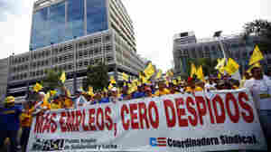 """Public workers march with a banner that reads in Spanish """"More jobs, zero layoffs"""" in San Juan on Oct. 15, 2009. Thousands of protesters gathered at Puerto Rico's financial hub to demonstrate against Gov. Luis Fortuno and the layoffs of more than 20,000 public employees."""