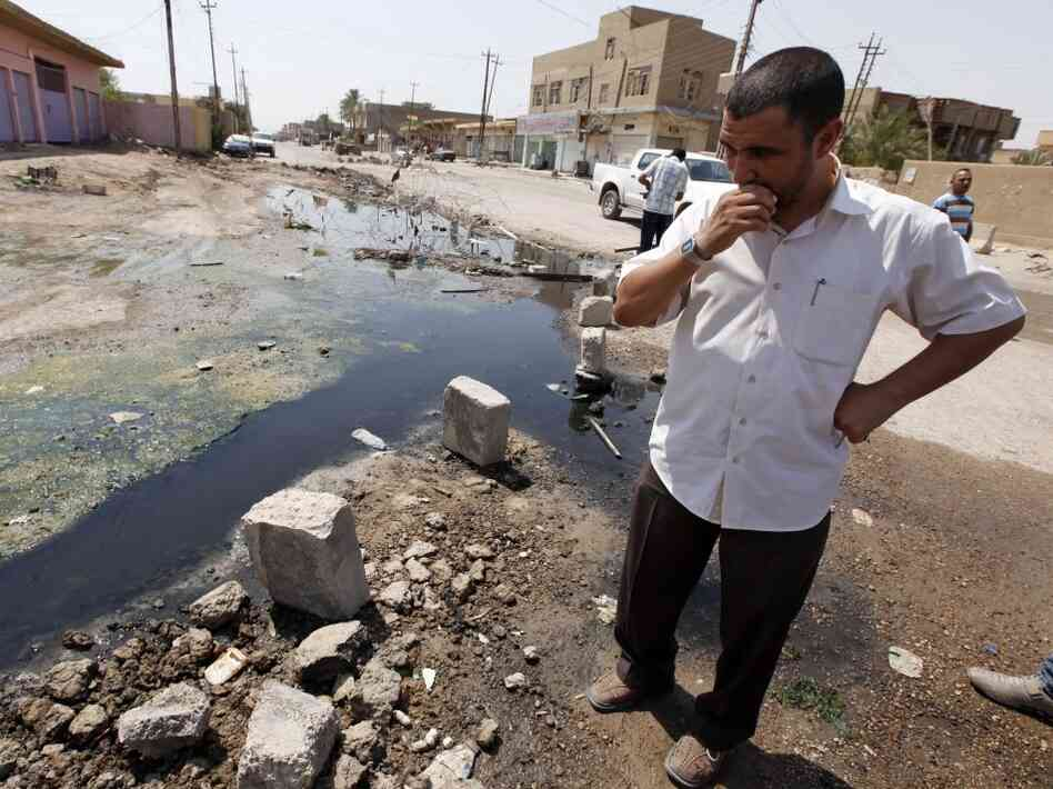 A man stands in a sewage-filled street in Fallujah in 2010. The Fallujah wastewater treatment system was left unfinished more than four years past the initial deadline. The sewage facility is among hundreds of projects funded by U.S. taxpayers that remain abandoned or incomplete, wasting more than $5 billion, according to auditors.