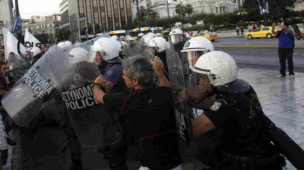 Riot police officers push back a protester during an anti-austerity protest Sunday in front of the Greek Parliament in Athens.