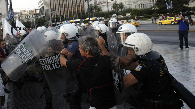 Riot police officers push back a protester during an anti-austerity protest Sunday in front of the Greek Parliament in Athens. (AP)