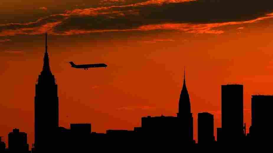 A plane flies past the Manhattan skyline at sunset.
