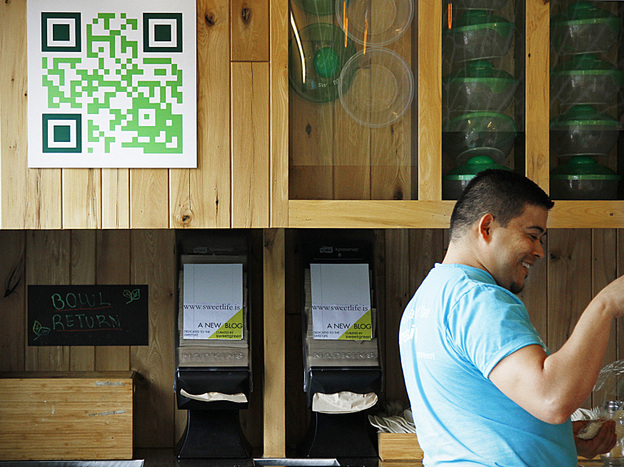 Manuel Martinez, the manager of a popular salad restaurant in Washington, D.C., called Sweetgreen, assists a customer. Martinez says customers use the QR code on the wall to learn about promotions and to get discounts.