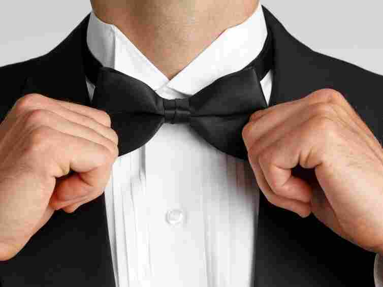 An uptight man straightens his bow tie.