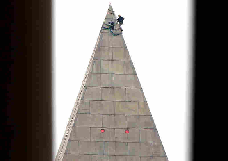 Suspended by ropes, an engineer begins the process of conducting a block-by-block inspection of the Washington Monument's exterior on Tuesday.