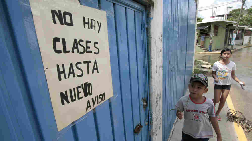 In Acapulco, Mexico, teachers are out on strike at more than a hundred schools because of spiraling violence related to the country's drug war. Here, a child looks at a sign announcing the closure of a school in Acapulco, Sept. 1.
