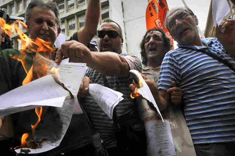 Greek public sector employees burn their tax notices outside the Finance Ministry in Athens last week.