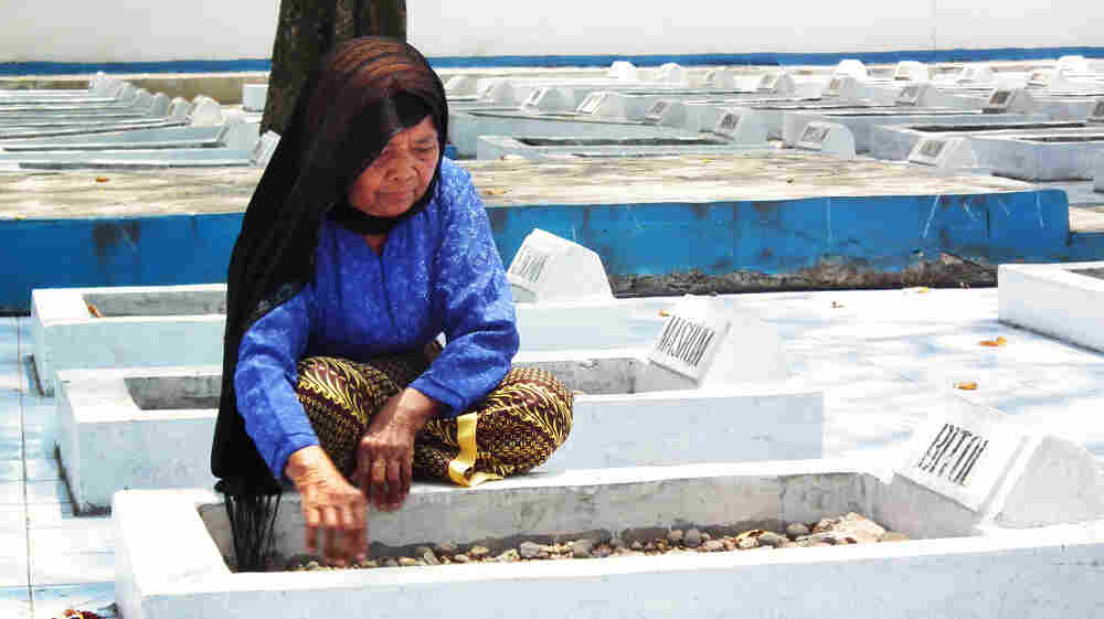 Cawi Binti Baisan, 84, squats beside the grave of her first husband, Bitol, a farmer who was executed by Dutch soldiers in 1947. She is one of seven remaining widows of the more than 400 estimated massacre victims. A Dutch court recently ruled that the Dutch government must compensate the widows for their losses.