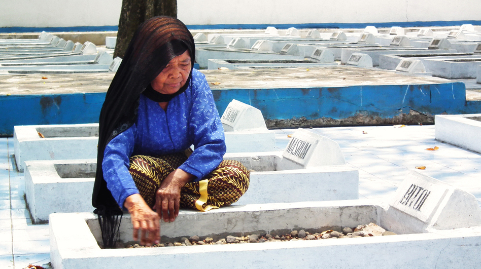<p>Cawi Binti Baisan, 84, squats beside the grave of her first husband, Bitol, a farmer who was executed by Dutch soldiers in 1947. She is one of seven remaining widows of the more than 400 estimated massacre victims. A Dutch court recently ruled that the Dutch government must compensate the widows for their losses.</p> (Yosef Riadi for NPR)